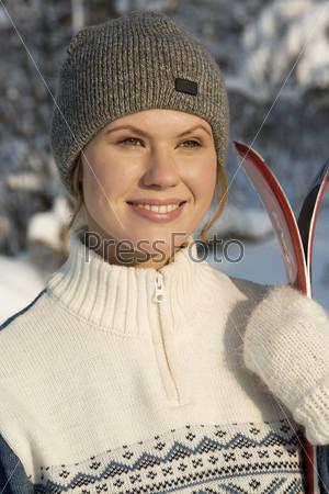 Девушка в варежках держит лыжи