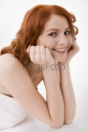 Портрет рыжеволосой улыбающейся девушки на белом фоне