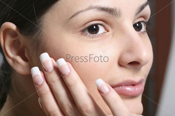 Портрет девушки без макияжа с рукой у лица