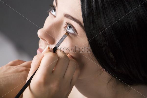 Девушке наносят макияж на глаза