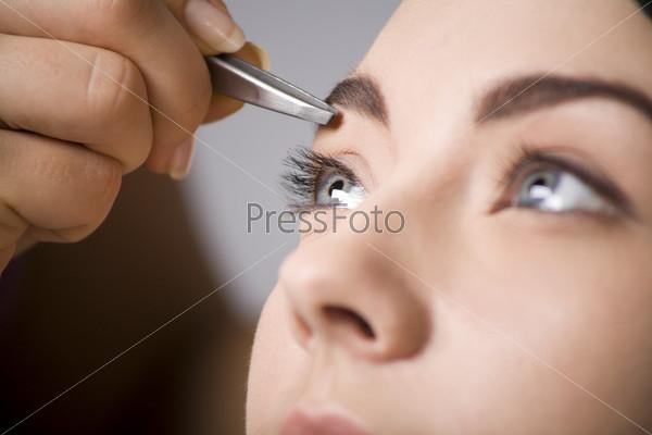 Девушке делают коррекцию бровей