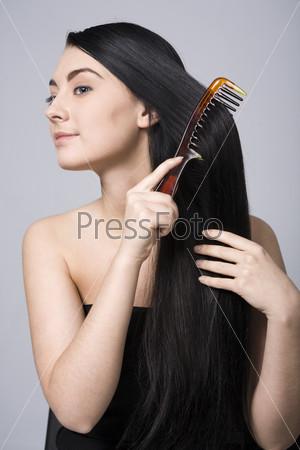Девушка расчесывает длинные волосы