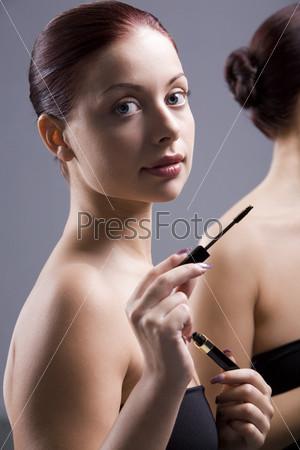Красивая девушка у зеркала с тушью для ресниц в руках