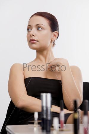 Красивая девушка и полочка с косметикой на переднем плане