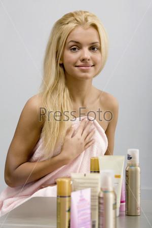 Девушка в полотенце и полочка с косметикой на переднем плане