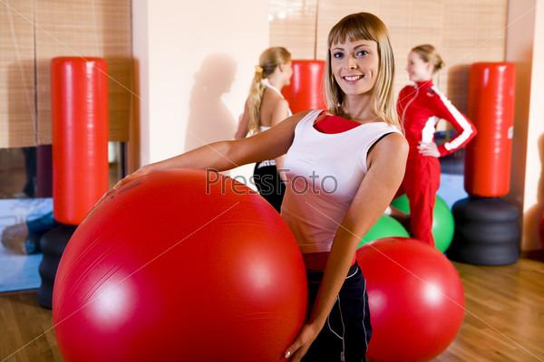 Спортивная девушка с красным шаром