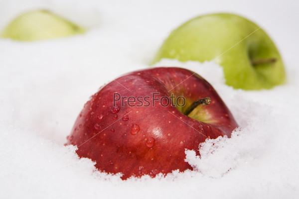 Красное и зеленое яблоко на снегу