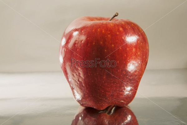 Красное яблоко на зеркальной поверхности