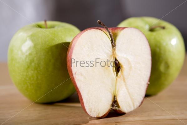 Два зеленых яблока и половинка красного яблока