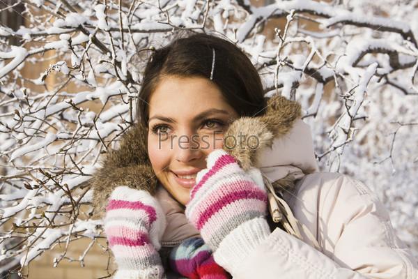 Красивая девушка в зимней одежде на фоне дерева