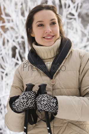 Девушка с лыжными палками в руках на фоне зимней природы
