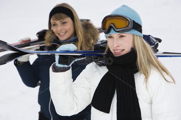 Девушки с горными лыжами на белом фоне