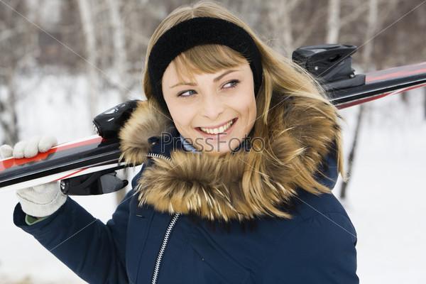 Красивая девушка с горными лыжами на плече на фоне зимнего леса