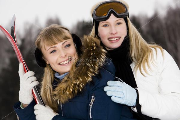 Красивые девушки на фоне зимнего леса с лыжами