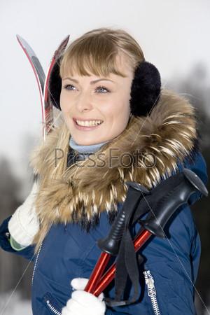 Красивая девушка с лыжами на фоне зимней природы