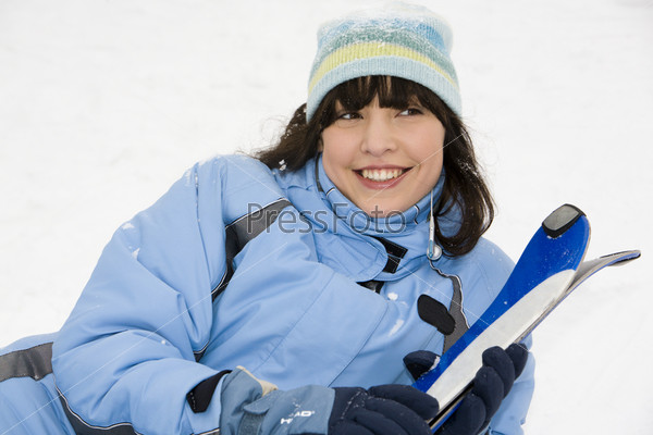 Девушка лежит на снегу с лыжами
