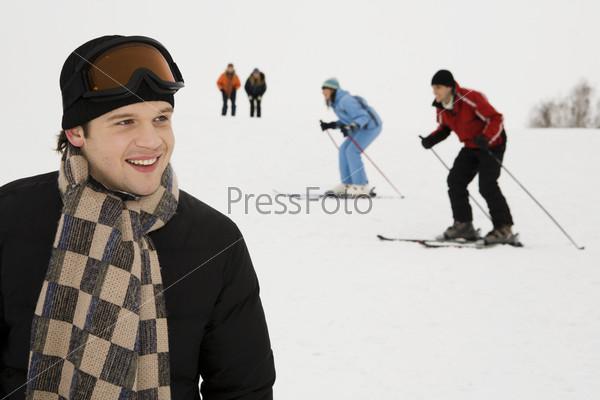Молодой мужчина на фоне лыжной трассы