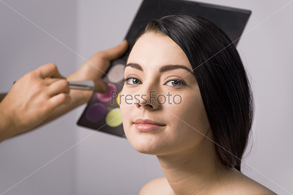 Девушка и косметика на заднем фоне