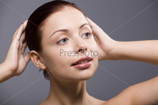 Молодая девушка поправляет прическу