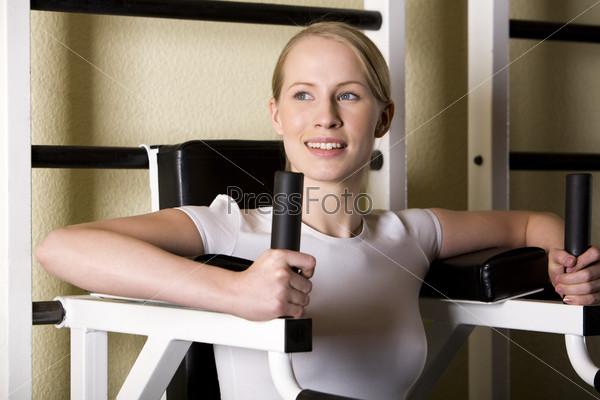 Красивая молодая блондинка занимается спортом на тренажере