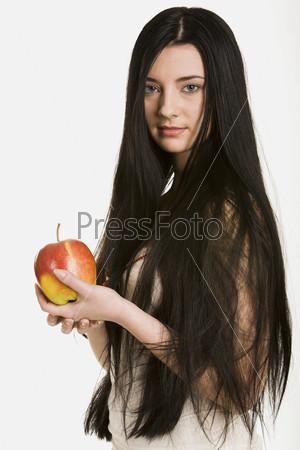 Красивая молодая женщина с распущенными длинными темными волосами на белом фоне с большим яблоком в руках