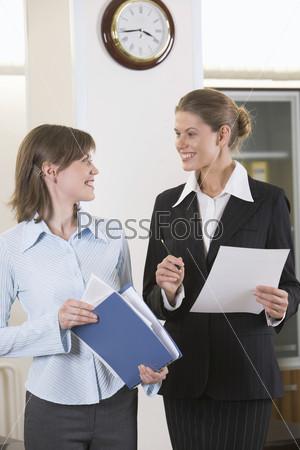 Две улыбающиеся темноволосые женщины с документами в руках обсуждают детали проекта