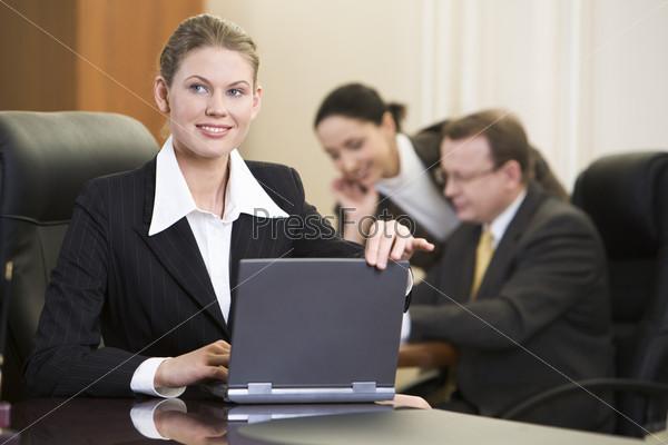 Деловая женщина открывает ноутбук и начинает работу в офисе