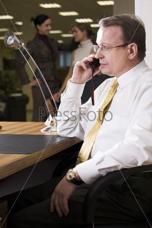 Бизнесмен в очках ведет серьезный разговор по мобильному тедлефону