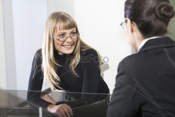 Две молодые сотрудницы разговаривают с интересом