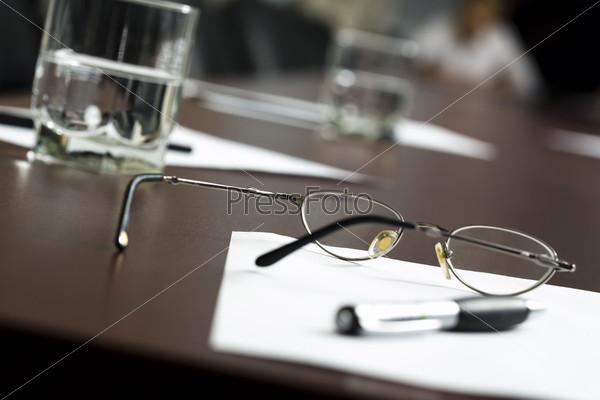 Стакан с минеральной водой, очки, документ и ручка лежат на столе