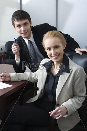 Красивая блондинка в сером пиджаке и молодой брюнет общаются в непринужденной атмосфере офиса