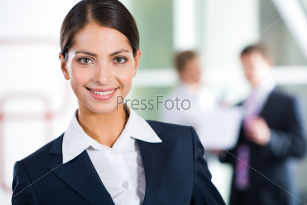 Portrait of clever businesswoman looking at camera in the room with two businesspeople on the