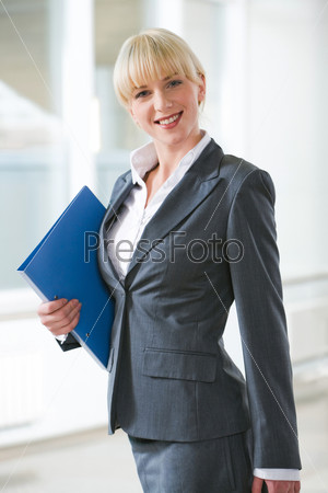 Portrait of confident woman with folder standing in the