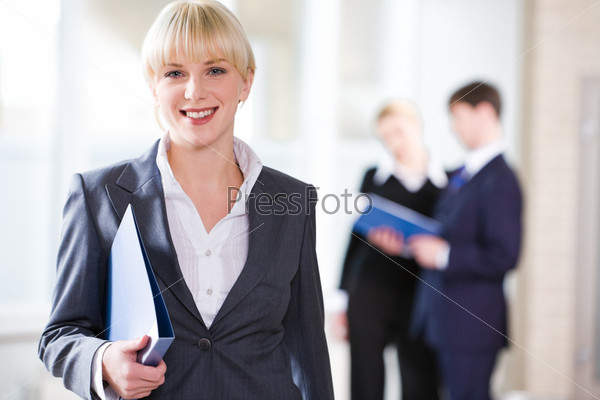 Portrait of young pretty professional holding a folder on the background of people