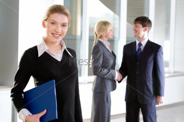 Портрет красивой служащей, держащей папку на фоне других людей, пожимающих друг другу руки