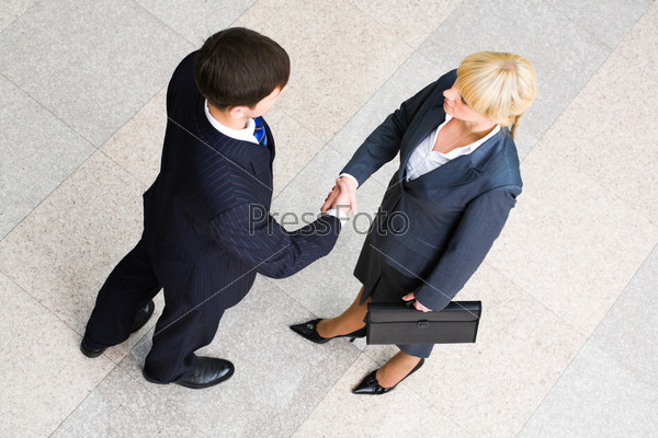 Image of business people standing and shaking hands in the room