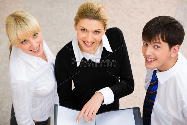 Image of three smiling business people looking at camera