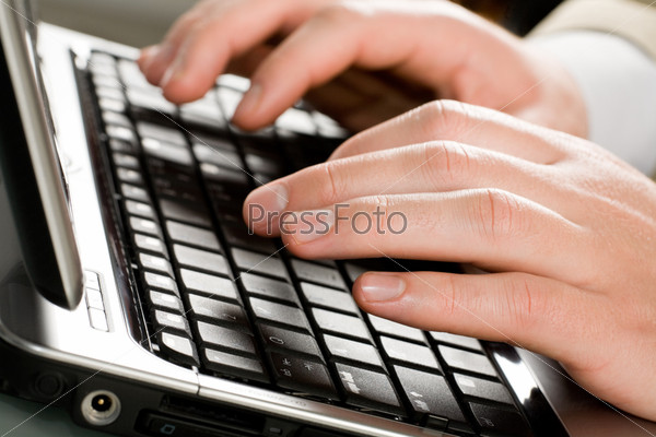Image of male hands typing a letter on the laptop