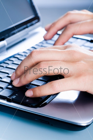 Image of a woman's hands typing a letter on the laptop