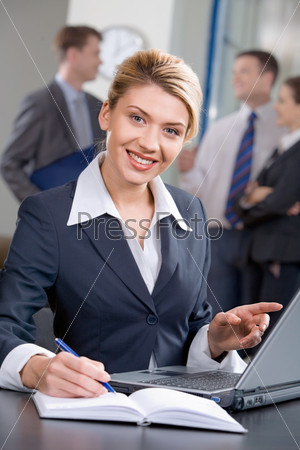 Portrait of strong woman sitting at the table and pointing at monitor of laptop in the office