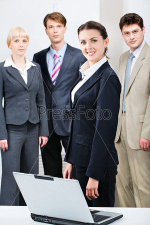 Confident woman in suit standing in front of business people