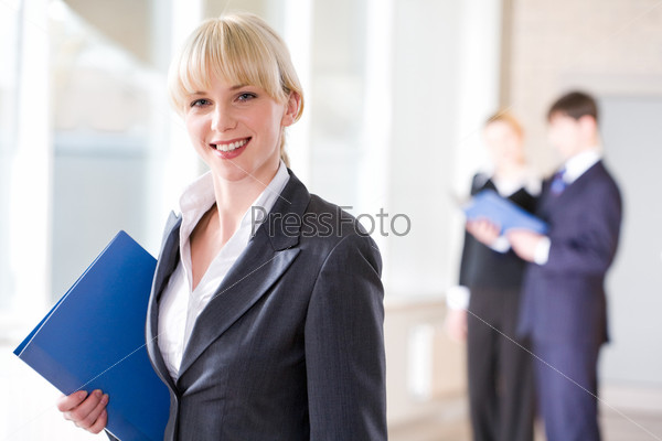 Attractive specialist in suit holding a grey folder on the background of people