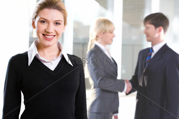 Красивая женщина на фоне людей, обменивающихся рукопожатием