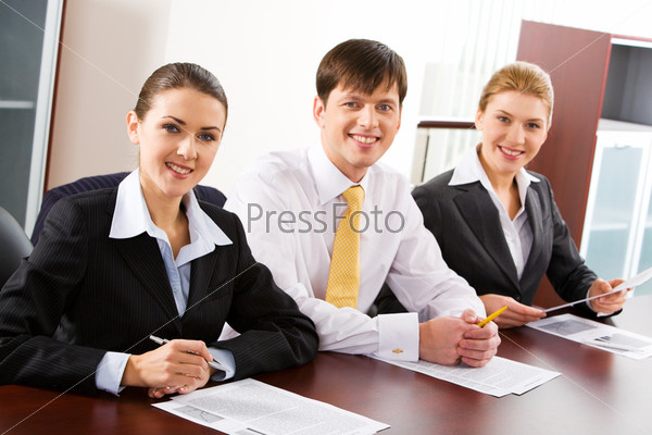 Image of three business people sitting at the table in a line