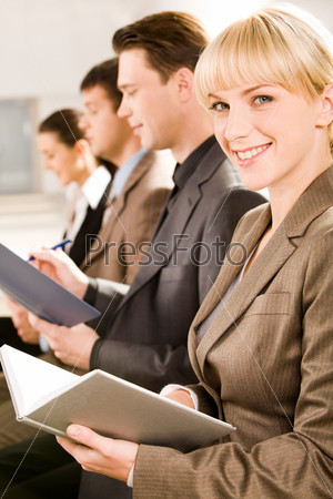 Image of business woman glancing at camera during a seminar