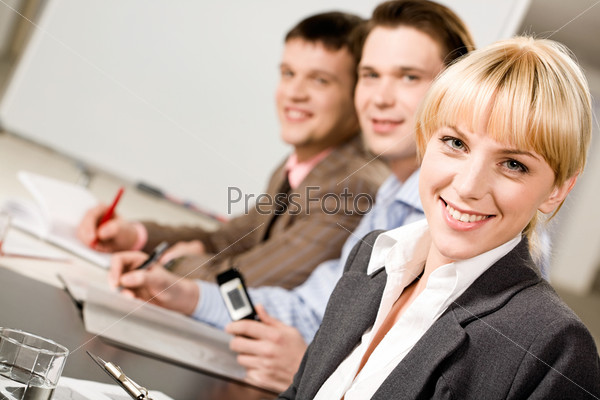 Portrait of pretty employee looking at camera on the background of business men