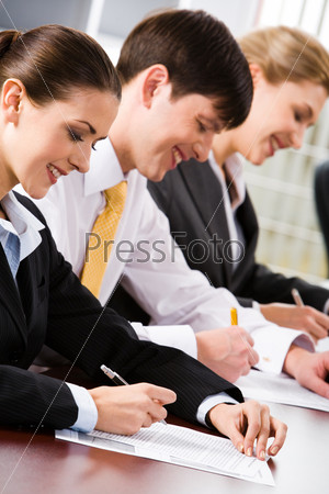 Three business people sitting at the table writing and smiling
