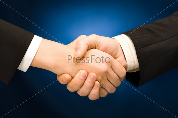 Business handshake - making a deal over a blue background