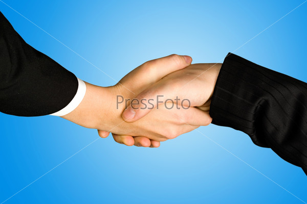 Photo of shaking hands making an agreement on a blue background