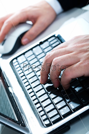 Vertical image of human hands typing a letter